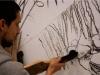 À San Vicente un entraînement - Un commandant dit «brûlez !» et 18 fusils dessinent une forêt, 2010, action sur plusieurs jours et installation, 18 fusils en bois taillés à la machette, certains partiellement brulés, pièces uniques. Dessin mural au bois brulé, dimensions variables. Dictaphone et mini-cassette avec document sonore, éditions limitées